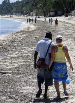 Older white woman on beach in Kenya with black escort